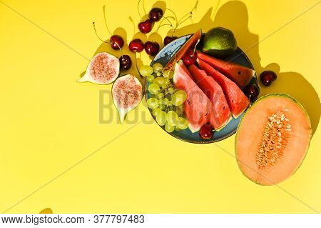 Different Fruits On A Yellow Background. Watermelon, Melon, Figs, Grapes, Cherries, Juicy And Ripe.