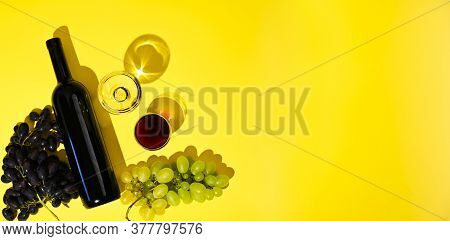 Two Glasses Of Red And White Wine, A Bottle, Grapes On A Yellow Background. The Concept Of Italian W