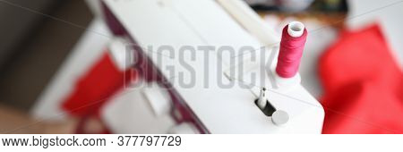 Close-up Of Reel Of Red Thread On White Sewing Machine. Professional Device For Sew Clothes. Process