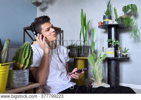 Portrait Of Teenage Boy 16 Years Old In Headphones Listening To Music, Audiobooks, Lessons. Home Int