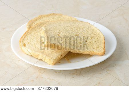 Few Slices Of Wheat Bread Dried Enough To Make Bread Crumbs On A White Plate Over A Kitchen Table. I