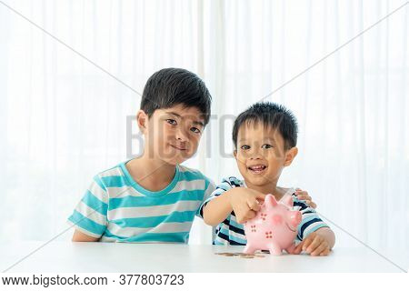 Two Asian Cute Brother And Son Insert Coin  In Piggy Bank Together On The Table In Living Room At Ho