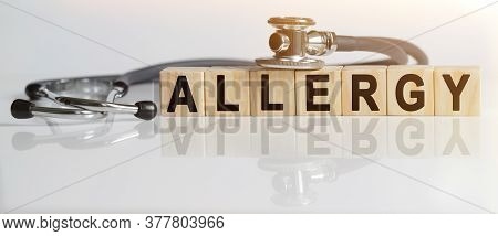 Allergy The Word On Wooden Cubes, Cubes Stand On A Reflective White Surface, On Cubes - A Stethoscop