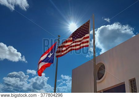 The American And Puerto Rican Flags Flying Under A Sunny Sky