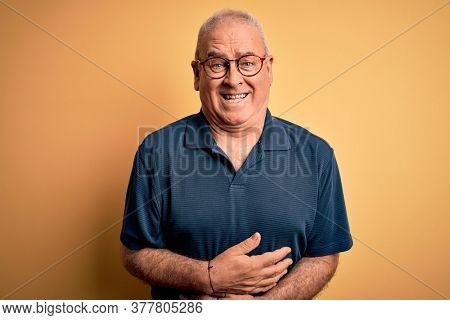 Middle age handsome hoary man wearing casual polo and glasses over yellow background smiling and laughing hard out loud because funny crazy joke with hands on body.