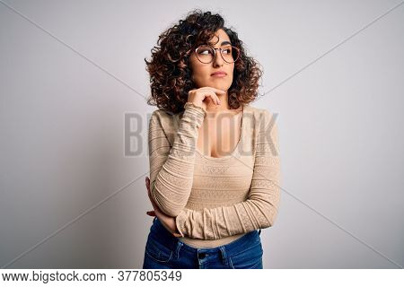 Young beautiful curly arab woman wearing casual t-shirt and glasses over white background with hand on chin thinking about question, pensive expression. Smiling with thoughtful face. Doubt concept.