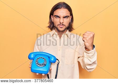 Young handsome man holding vintage telephone annoyed and frustrated shouting with anger, yelling crazy with anger and hand raised