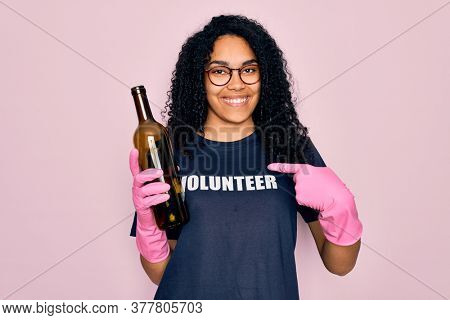 African american curly woman wearing volunteer t-shirt doing volunteering recycling glass bottle with surprise face pointing finger to himself