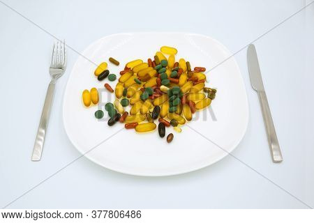 Many Different Weight Loss Pills And Supplements As Food On White Plate With Fork And Knife. Diet Pi