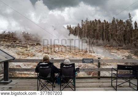 Yellowstone National Park - June 28, 2020: Two Tourists Camp Out With Chairs, Waiting For The Steamb
