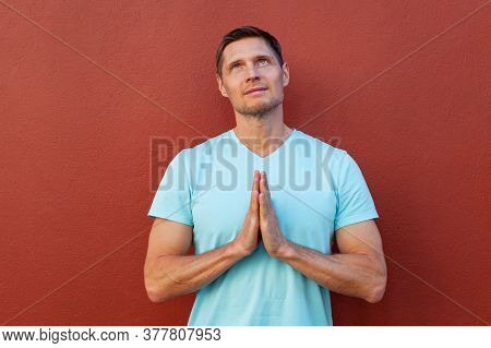 Handsome Man Clasp His Hands In Prayer, Looking At The Sky, Standing Against Red Background. Portrai