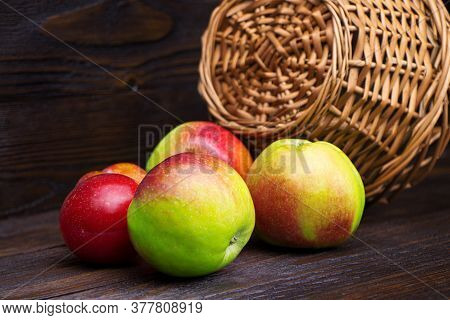 Apples And Plums On A Brown Wooden Background. Fresh Fruits. Harvest. Healthy Food. A Wicker Basket.