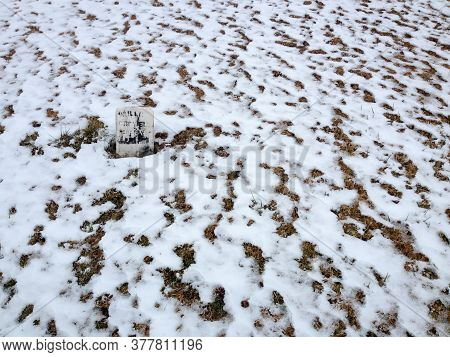 Solitary Headstone At Graveyard Cemetery With Snow On White Winter Day