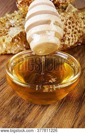 Yellow Honey And Honeycomb Slice On A Wooden Table