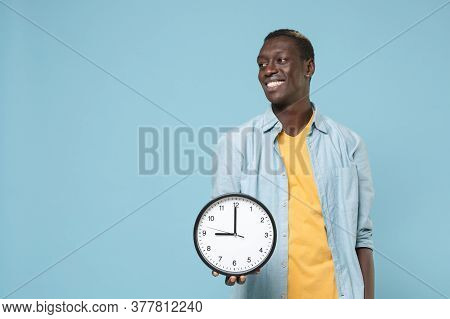 Smiling Young African American Man Guy In Casual Shirt Yellow T-shirt Isolated On Blue Wall Backgrou