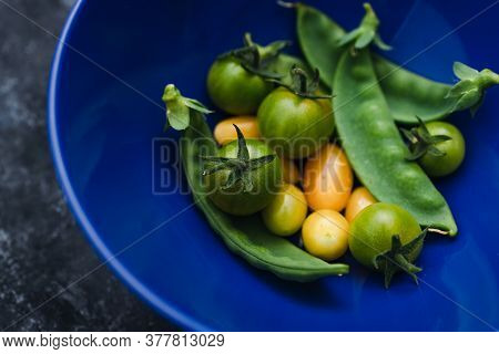 Simple Food Ingredients Concept, Bowl With Freshly Picked Snowpeas And Tiny Yellow And Green Tomatoe