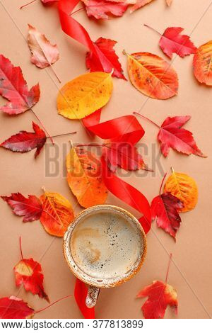 Floral Autumn Background. A Up Of Coffee On The Beige Background With Yellow And Red Falling Leaves