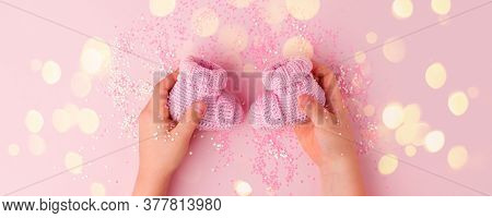 Pink Shoes For Newly Born Baby Girl In Kids Hands On Pink Background, Concept Of Expectation Of Baby