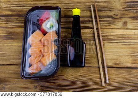 Sushi Rolls Philadelphia In Plastic Box On Wooden Table. Top View. Sushi For Take Away Or Delivery O