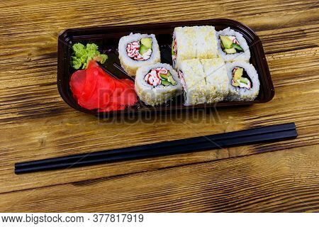 Uramaki Sushi Rolls With Surimi In Plastic Box On Wooden Table. Top View. Sushi For Take Away Or Del