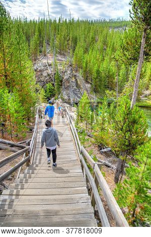 Wyoming, Usa - Aug. 24, 2019: Visitors Walking Down Wooden Stairs Toward Firehole River In Yellowsto