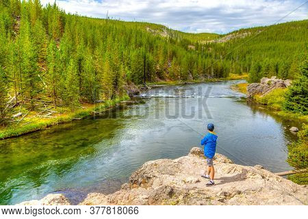 A Young Visitor Looking Toward Firehole River In Yellowstone National Park, Wyoming, Usa. The River