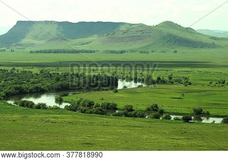 A Picturesque Valley With A Winding River Flowing Through It And High Mountains In The Background.