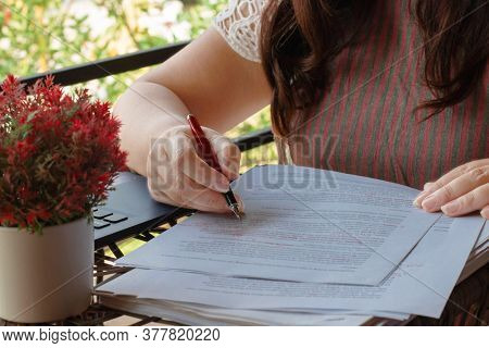 Woman's Hand Holding Pen Working On Blurred Paperwork