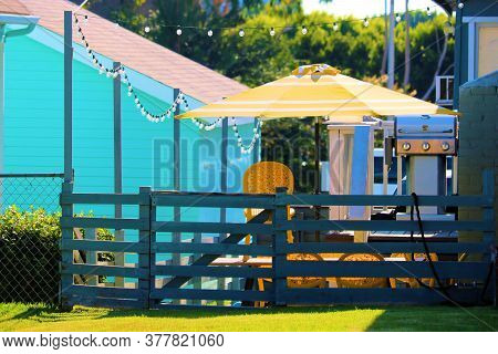 Wooden Fence Surrounding A Furnished Outdoor Deck Including An Umbrella, Table, Chairs, And A Barbeq