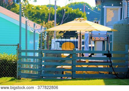 Outdoor Deck With Contemporary Hanging Lights Above A Barbeque, Umbrella, Table, And Chairs Taken At