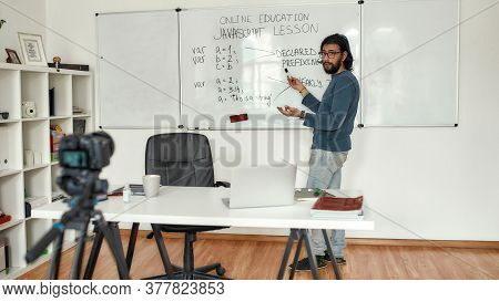 Javascript Lesson. Young Bearded Male Teacher Wearing Glasses Pointing At Whiteboard And Teaching Ja