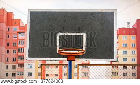 Black Orange Basketball Hoop On Backboard At Sports Ground Against Grid Fence And Dwelling Buildings