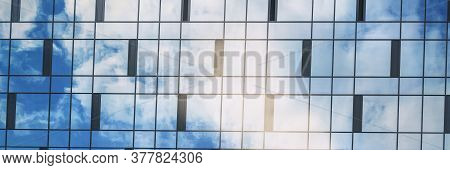 Blue Sky With White Clouds Reflects In Highrise Building Panoramic Windows On Summer Day Close Horiz