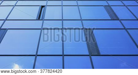 Local Commercial City Building With Panoramic Glass Windows Reflecting Blue Skyscape Under Bright Su