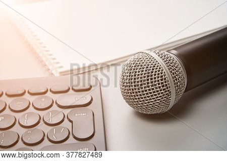 Podcast Concept. White Notebook With Blank Sheet. Black Microphone And Keyboard. Audiobook And Podca