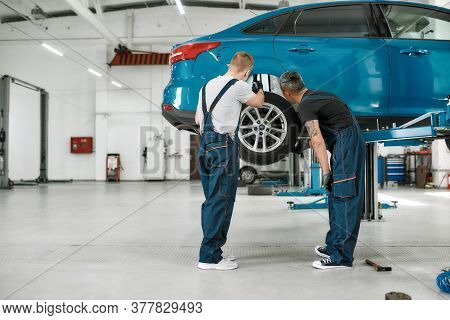 Full Length Shot Of Two Male Mechanics Using Torch For Inspecting Wheel Of Lifted Car At Auto Repair