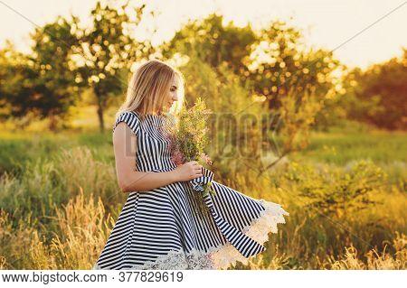 Portrait Eco-friendly Woman In Striped Sundress On Meadow With Bouquet Of Wildflowers In Hand Dancin
