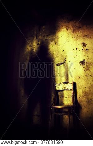 A Ghost Like Shadow Near An Old Wood Chair In A Dark Scary Basement.
