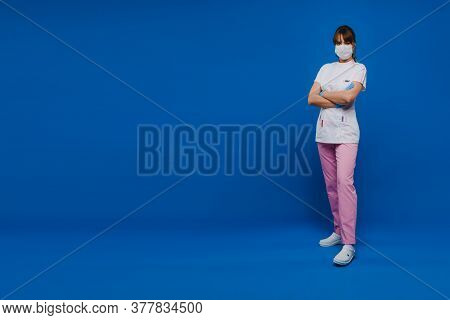 A Female Doctor Stands In A Medical Mask, Isolated On A Blue Background.a Nurse In White Clothes On