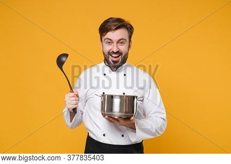 Cheerful Young Bearded Male Chef Cook Or Baker Man In White Uniform Shirt Posing Isolated On Yellow