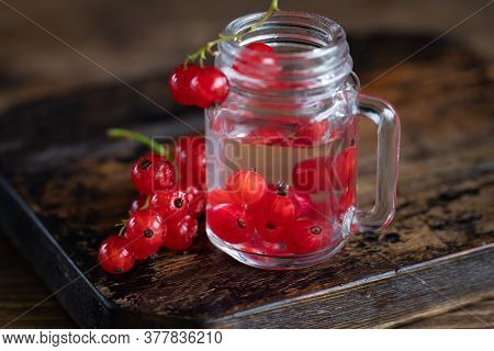 Homemade Liqueur In Shot Glass With Red Current Berries On The Table