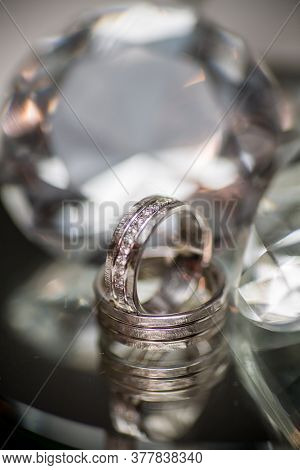 Wedding Rings On Diamond Shaped Glass Background. High Quality Photo