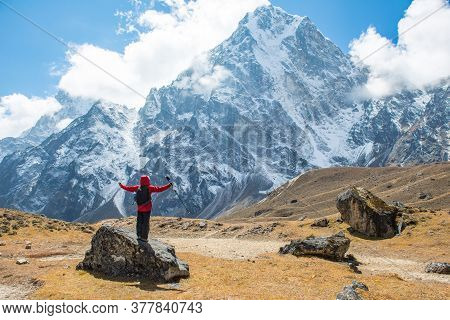 Trekker Standing On The Rock And Raised His Hands Up With The Spectacular View Of Mt.cholatse (6,440