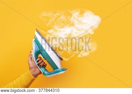 Modern Iron With Steam In Hand Over Yellow Background