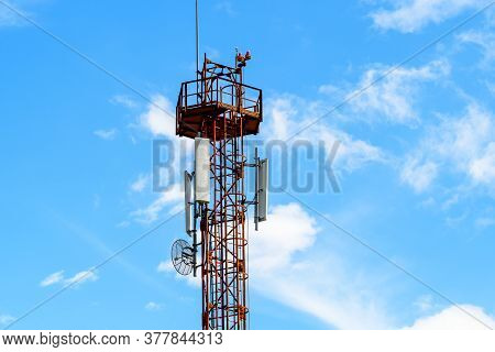 Telecommunications Antennas On A Red And White Telecommunications Tower With Clear Blue Sky In The B