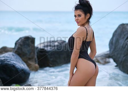 Portrait of young woman on tropical beach looking at camera. Beautiful latin girl in swimwear with copy space. Summer vacation and tanning concept.