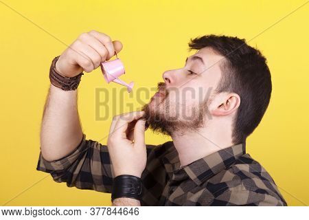 Cute Man With A Mini Watering Can In His Hand Watering His Beard, Beard Growth Concept Oil