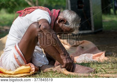 A Poor And Old Man From The Tribal Community Sleeping In The Sitting Position. The Lifestyle Of The