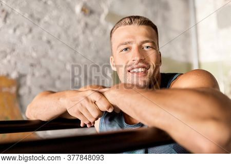 fitness, sport, training and lifestyle concept - smiling young man exercising on parallel bars in gym