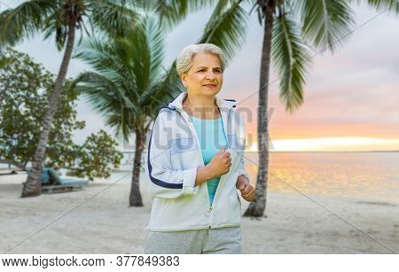 fitness, sport and healthy lifestyle concept - senior woman running over tropical beach background in french polynesia